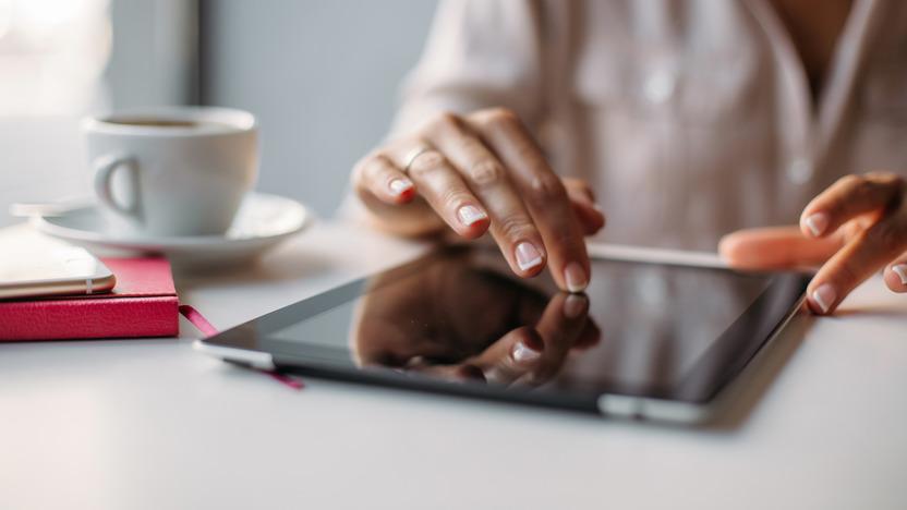 Eine Frau bedient ein iPad an einem Tisch, auf dem ein Kaffee steht