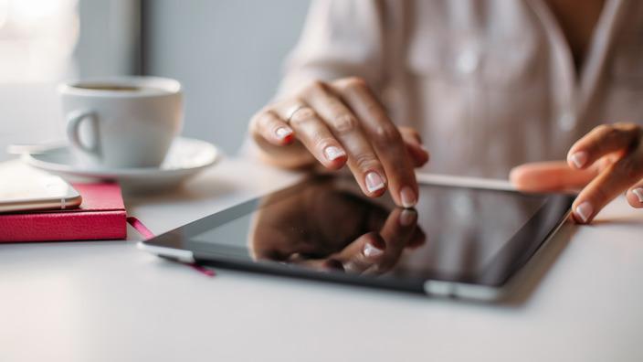 Frau lädt ein Formular auf ihrem Tablet herunter