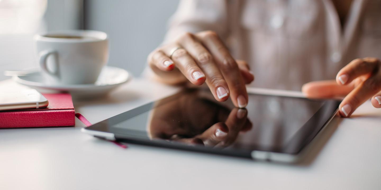 Frau tippt mit dem Zeigefinger auf ein Tablet um Formulare herunterzuladen