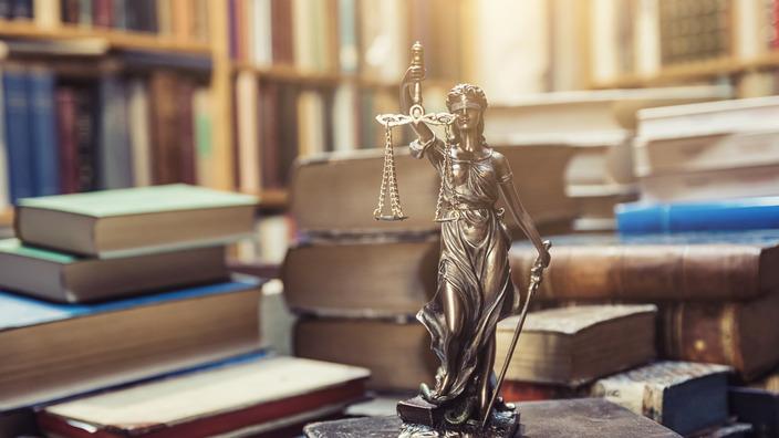 kleine bronzene Justitia-Statue steht auf einem Stapel Gesetzestexte