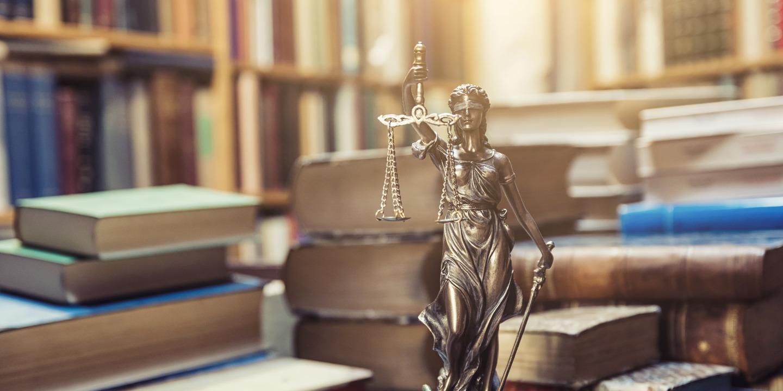 Justitia-Statue steht vor Stapeln von Büchern