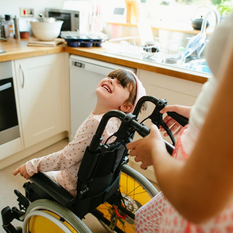 Frau schiebt ein kleines Mädchen im Rollstuhl durch eine Küche