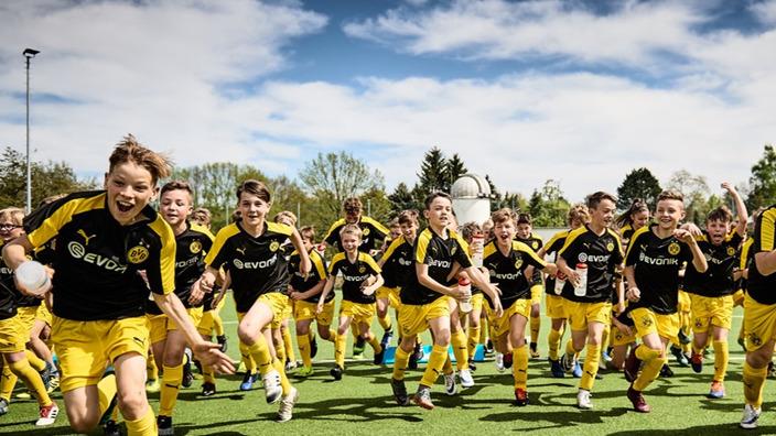 Fußballkids im BVB-Outfit rennen über den Rasen