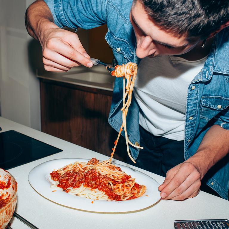 Student isst Spaghetti mit Tomatensoße im Stehen