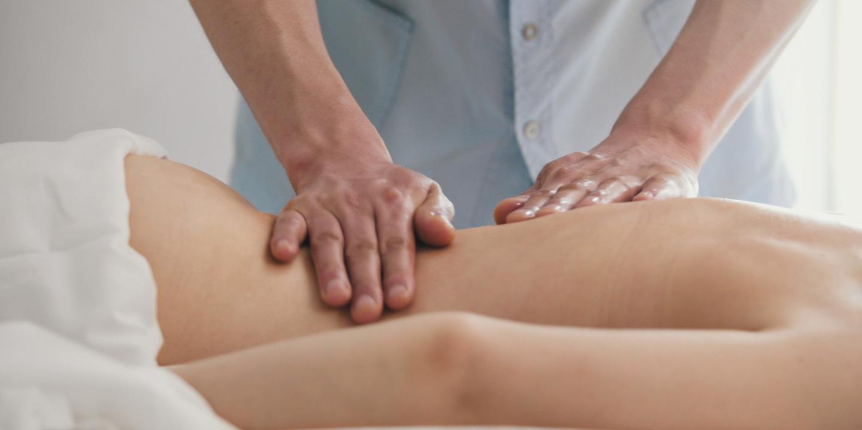 Hände eines Ostheopaten behandeln den Rücken eines Patienten.