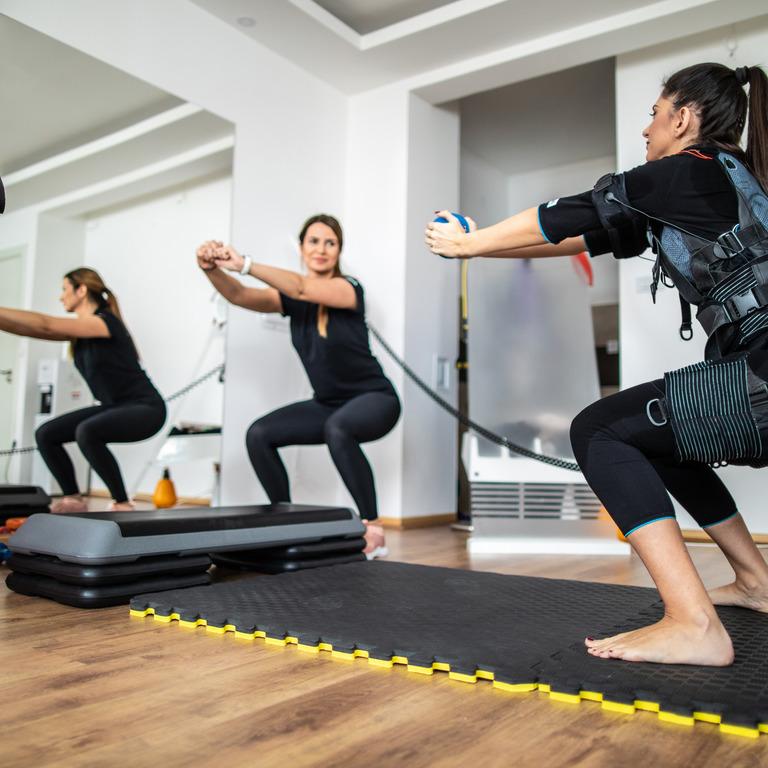 Frau trainiert in einem EMS-Studio mit einer Trainerin
