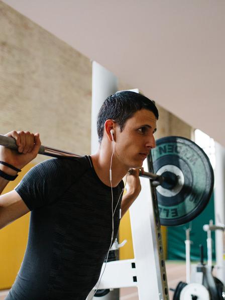 Mann trainiert mit Langhantel im Fitnessstudio