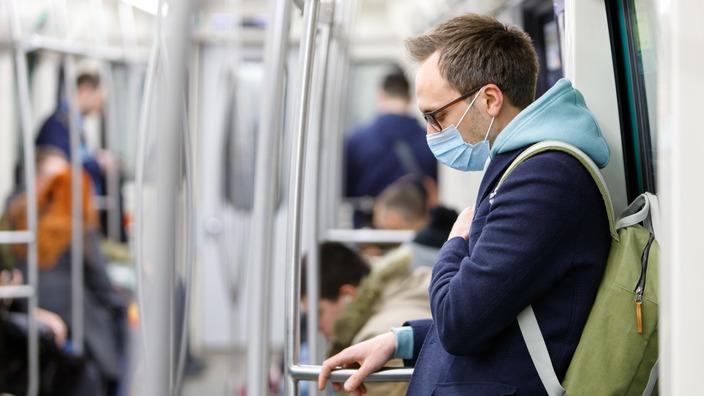 Pendler mit Atemmaske in der U-Bahn
