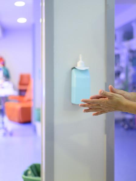 Krankenschwester desinfiziert ihre Hände