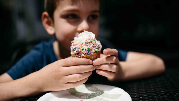 übergewichtiger Junge isst einen Muffin mit bunten Streuseln