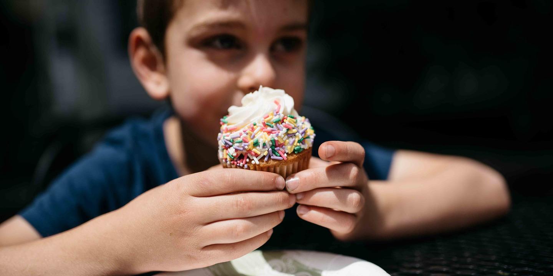 Junge hält einen Cupcake in den Händen.