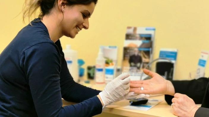 IKK-Gesundheitsexpertin Lisa Jumpertz piekst einer Versicherten in den Finger