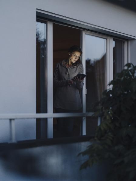 Frau steht an offenem Fenster und liest auf ihrem Tablet
