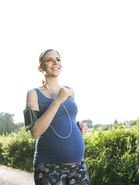 schwangere Frau joggt auf einem Feldweg