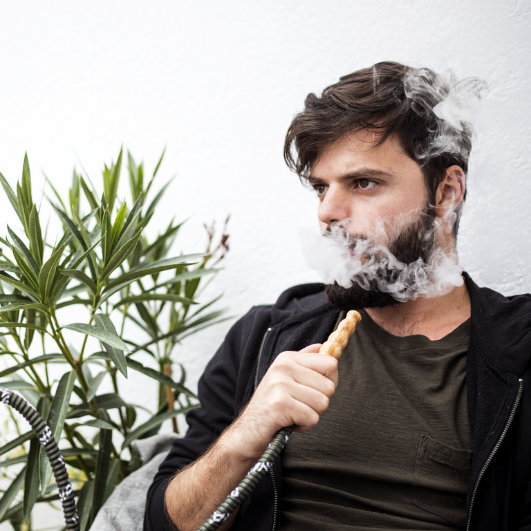 junger Mann raucht eine Shisha