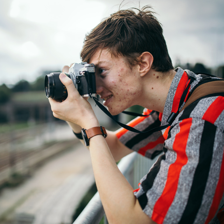 Teenager mit Hautunreinheiten fotografiert etwas