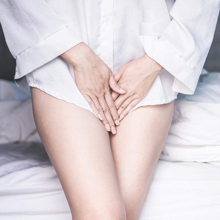 Frau steht mit überkreuzten Beinen und hält beide Hände vor ihren Schambereich