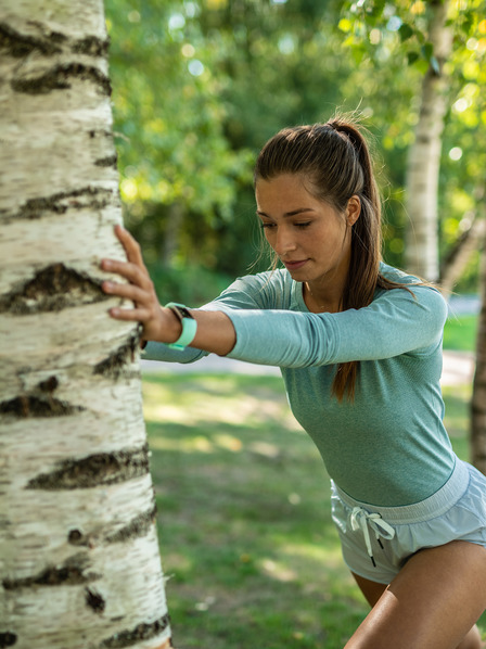 Frau dehnt sich nach dem Joggen an einem Baumstamm