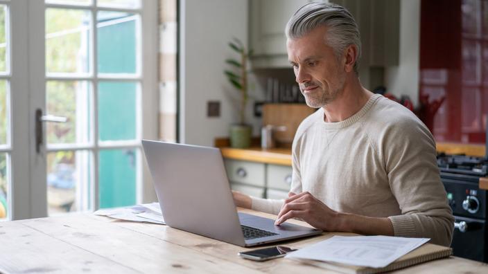 Ein Grauhaariger Mann mittleren Alters sitzt vor einem Laptop am Küchentisch.