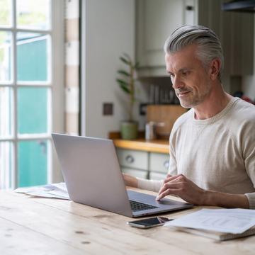 Mann sitzt zuhause am Laptop.