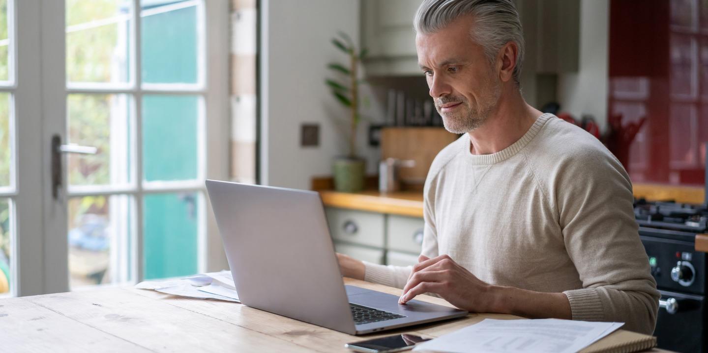 Grauhaariger Mann sitzt vor Laptop an Küchentisch.