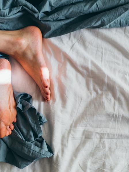 Nackte Füße einer Person, die im Bett liegt