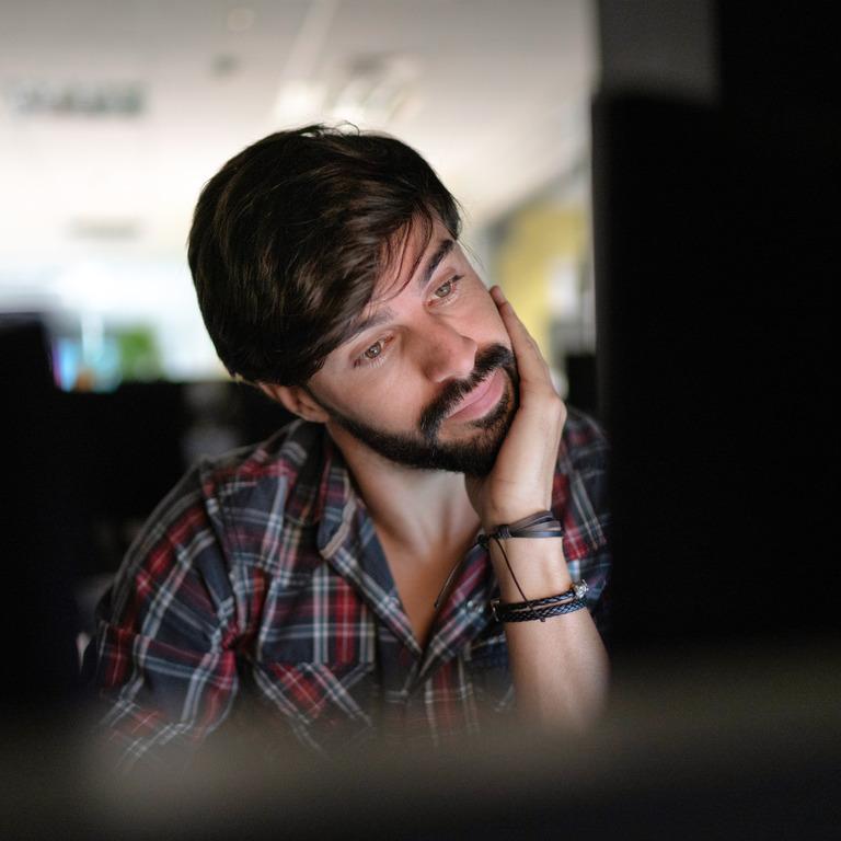 Mann sitzt nachdenklich vor seinem Rechner