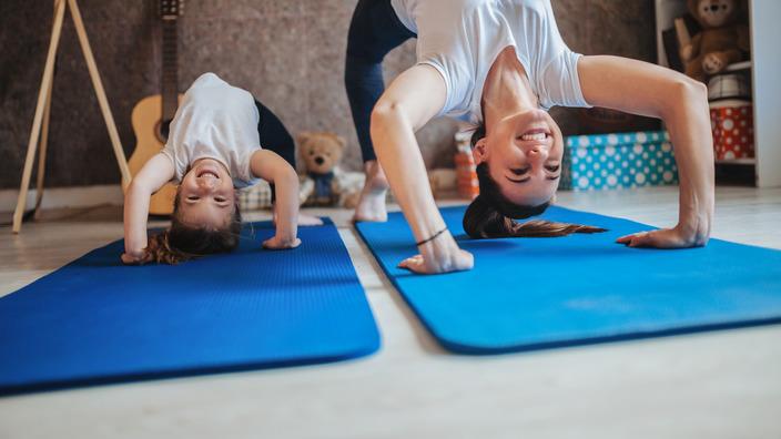 Mutter und ihre kleine Tochter machen nebeneinander eine Brücke auf einer Gymnastikmatte