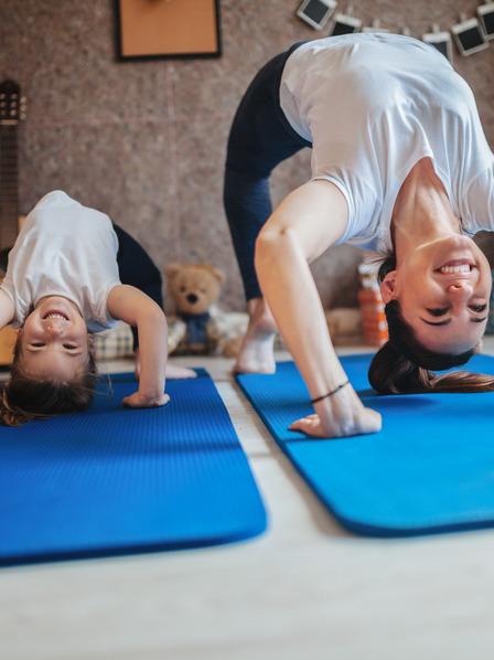 Mutter und ihre kleine Tochter machen eine Brücke auf einer Yoga-Matte