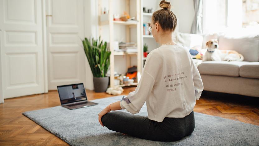 Frau sitzt auf dem Wohnzimmerboden und nimmt an einem Online-Kurs zur Entspannung teil