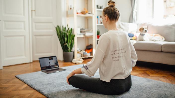 junge Frau sitzt im Schneidersitz auf dem Boden ihres Wohnzimmers und nimmt an einem Online-Sportkurs teil