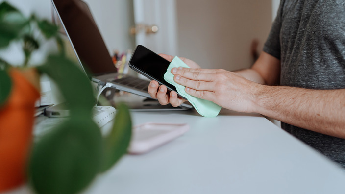 Mann säubert das Display seines Smartphones mit einem Tuch