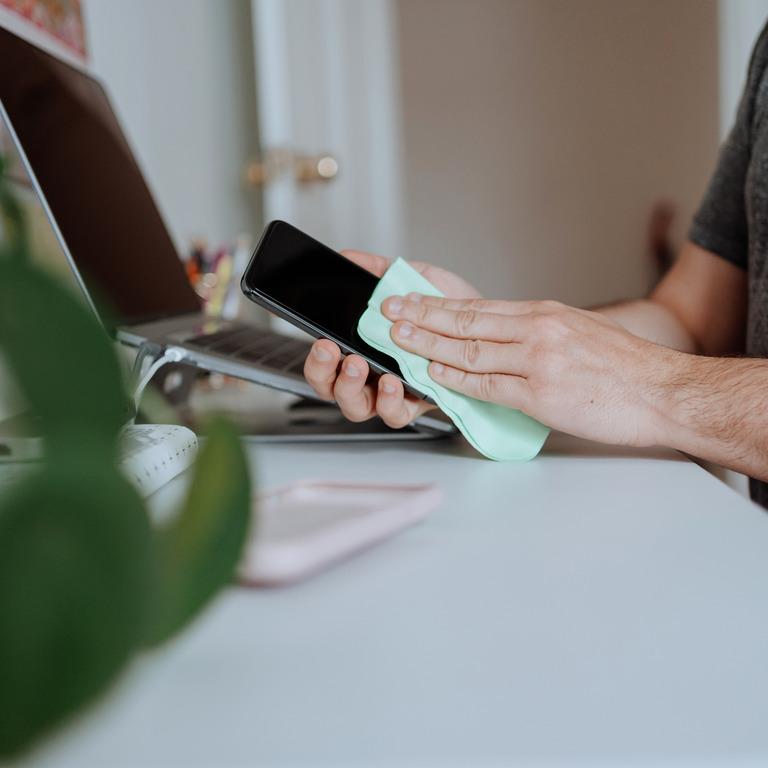 Hand wischt mit einem Mikrofasertuch über ein Smartphonedisplay