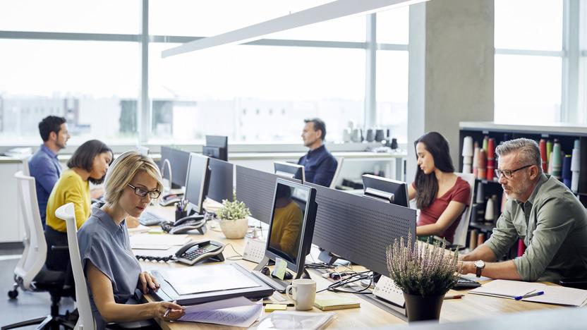 Sechs Menschen sitzen an einem großen Schreibtischblock