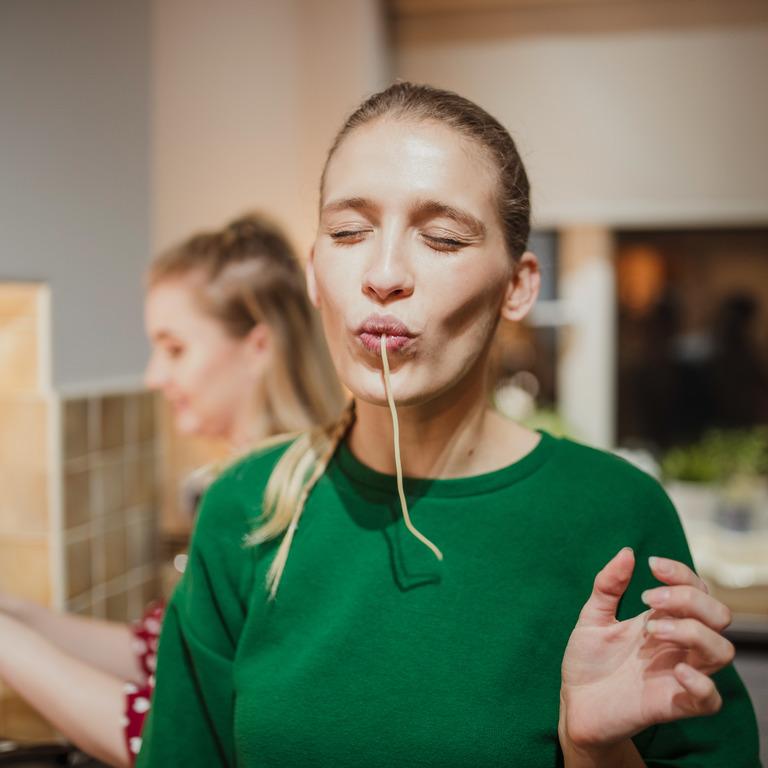 Frau steht in der Küche und genießt eine Spaghetti.
