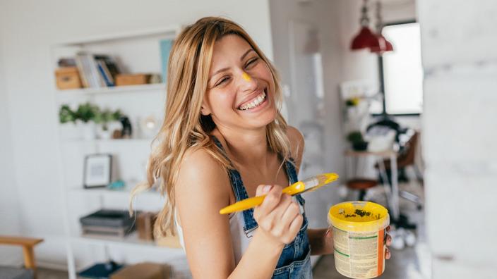junge Frau streicht ein Regal mit gelber Farbe