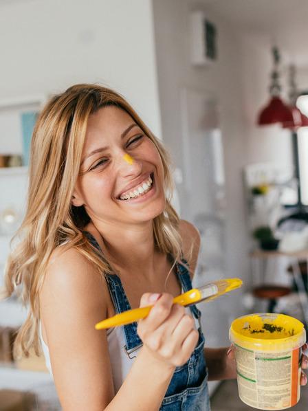 junge Frau bemalt einen Schrank mit gelber Farbe und hat Farbtupfen im Gesicht