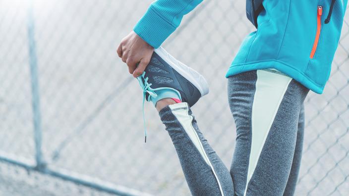 Joggerin dehnt ihr rechtes Bein