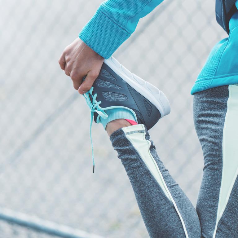 Frau in Laufkleidung dehnt ihr Bein nach hinten