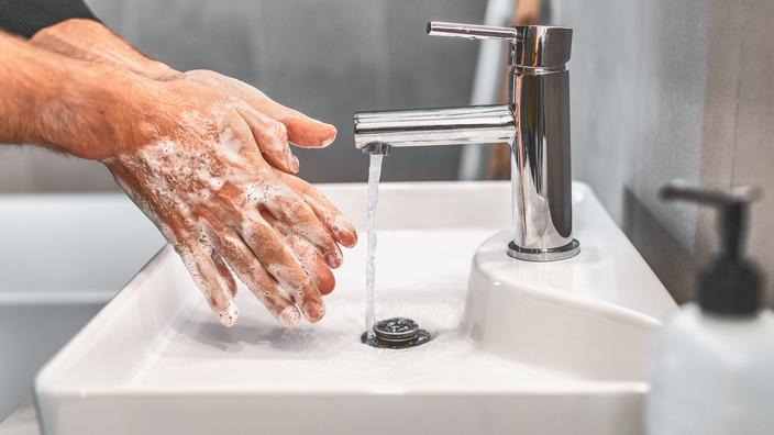 eingeseifte Hände und ein laufender Wasserhahn