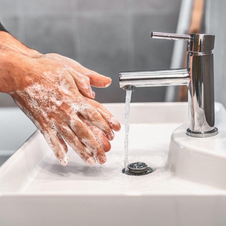 eingeseifte Hände unter einem laufenden Wasserhahn