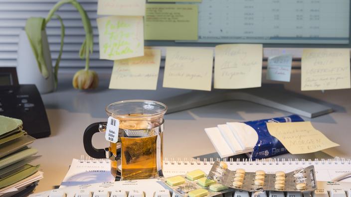 Arbeitsplatz mit Monitor und Tastatur, daneben steht ein Becher Tee