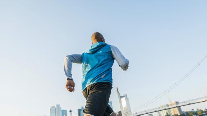Mann in Laufkleidung joggt am Flußufer entlang, im Hintergrund ist eine Brücke