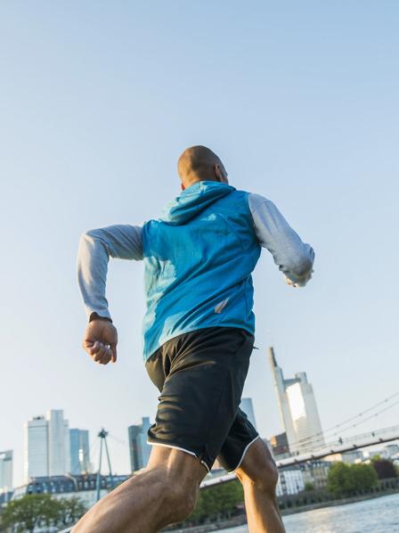 Mann in Laufklamotten joggt an Flußufer entlang, im Hintergrund ist eine Brücke