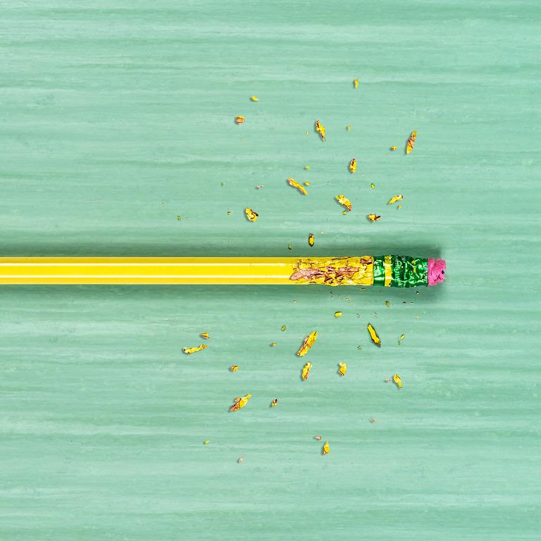 Ein gelber Bleistift mit rotem Radiergummi auf einem grünen Tisch, an dessen oberen Ende Späne vom darauf herumkauen liegen.