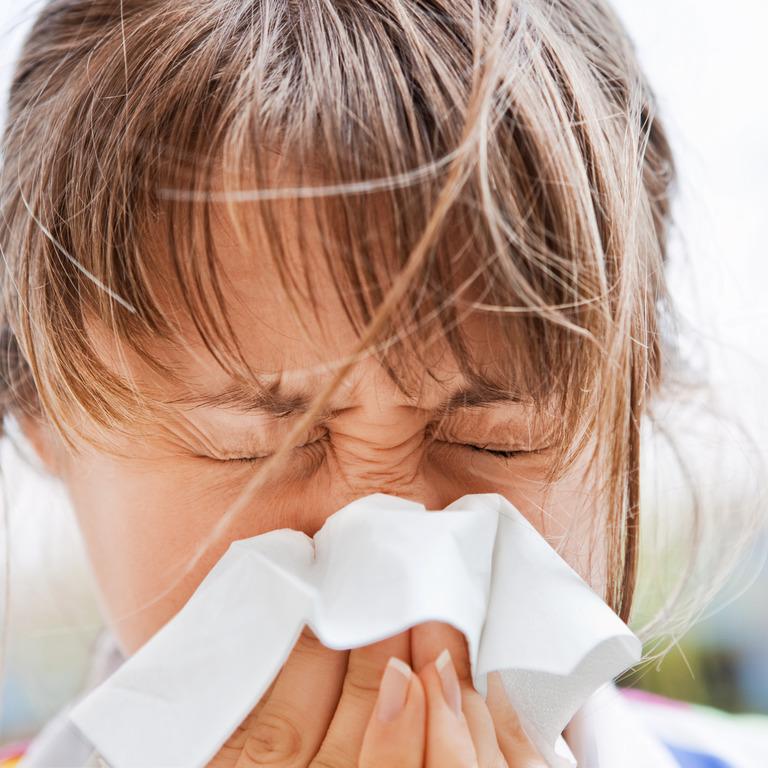 Junge Frau niest mit zusammengekniffenen Augen in ein Taschentusch