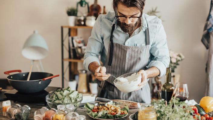 Mann träufelt selbst gemachtes Dressing über einen Teller Salat