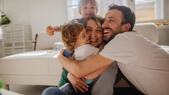 vierköpfige Familie nimmt sich gegenseitig in den Arm