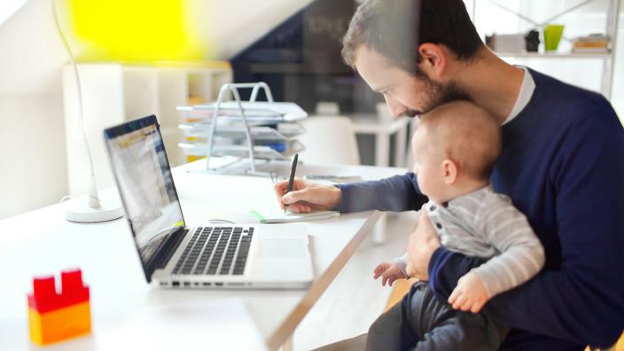 Vater sitzt mit seinem Sohn auf dem Schoß am Laptop