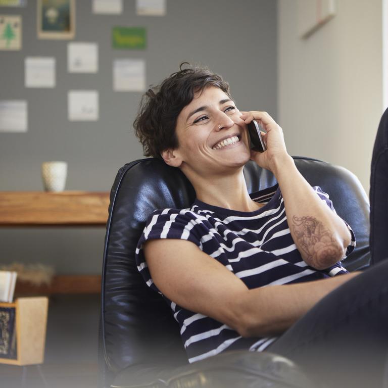gut gelaunte Frau sitzt in einem Lounge-Sessel und telefoniert